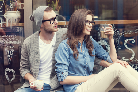 Stylish couple sitting with cup of coffee outside the cafe photo