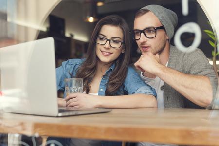 wifi internet: Pareja disfrutando de la conexi�n inal�mbrica a Internet en la cafeter�a Foto de archivo