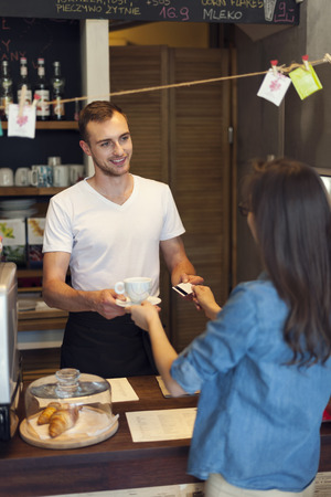 Woman paying for coffee by credit card photo