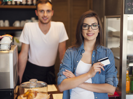 Smiling waiter and beautiful female customer with credit card  photo