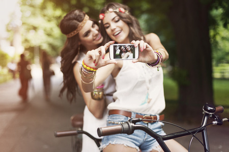 Hippie girls taking selfie at park  Stock Photo