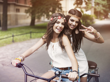 lovely girl: Portrait of funny boho girls on the tandem bicycle Stock Photo