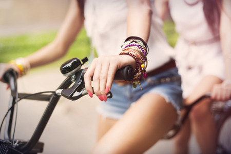 mujer hippie: Primer plano de las niñas que montan en bicicleta boho