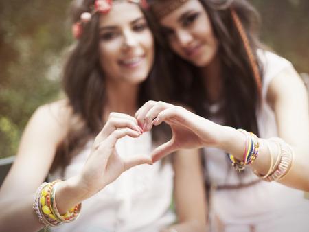 silhouette coeur: Boho filles montrant forme de coeur de mains Banque d'images