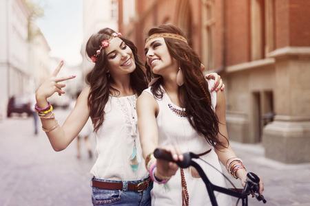 Boho girls walking alley of city  photo
