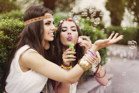 mujer hippie: Hippie dos chicas hermosas que soplan burbujas