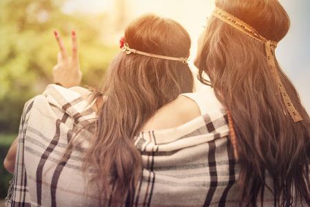 simbolo della pace: Boho amici femminili con la coperta a guardare il tramonto