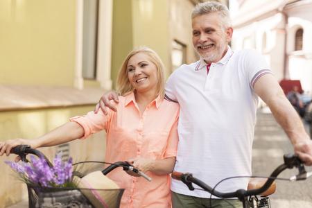 pareja madura feliz: Feliz pareja madura caminando con la bicicleta en la ciudad