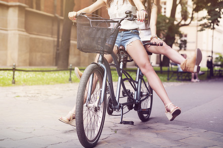 tandem bicycle: Part of boho girls legs during riding tandem bike Stock Photo