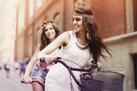 Boho girls riding a bike in city  photo