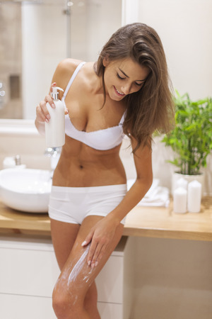 Young woman applying body lotion Stock Photo