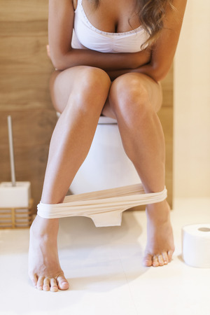 bending over: Woman on the toilet has problems with constipation