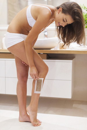 bending over: Woman waxing leg in bathroom  Stock Photo