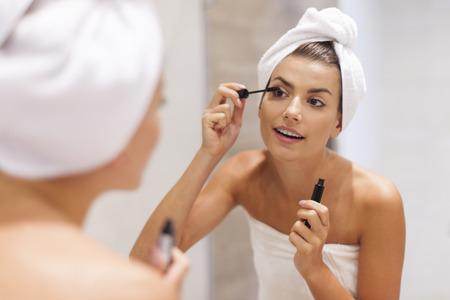 maquillaje de ojos: Mujer hermosa que usa el rimel en el ba�o