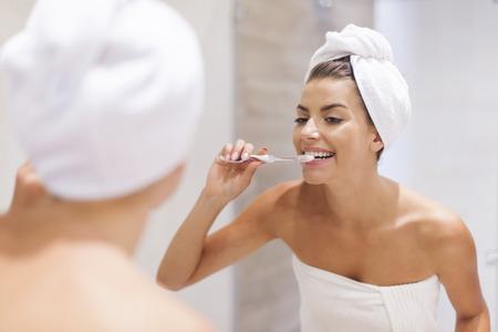 smile teeth: Young woman brushing teeth in bathroom