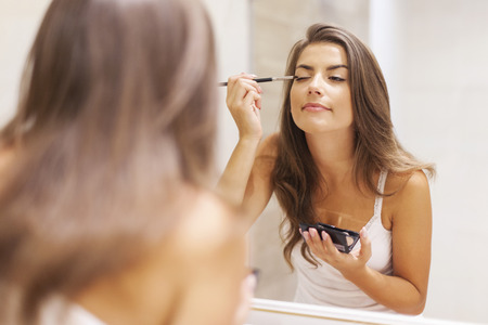 morning routine: Pretty woman applying eyeshadow in front of a mirror