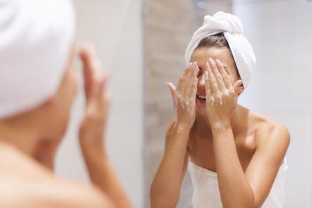 washing face: Woman washing face in bathroom