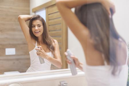 beautiful armpit: Young woman applying deodorant on underarm. Photo taken through glass Stock Photo