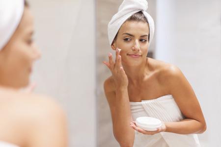 mujer maquillandose: Hermosa mujer aplicar crema hidratante en la cara