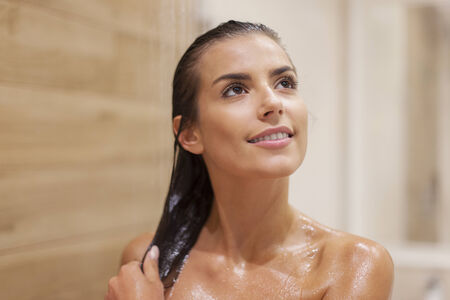 Attractive brunette woman taking shower photo