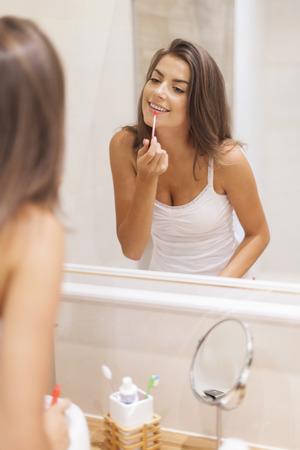 look in mirror: Beautiful woman applying lip gloss in bathroom