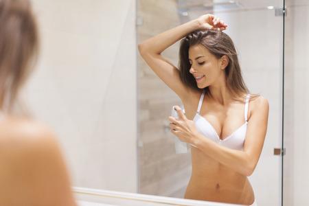 armpit: Mujer feliz que usa desodorante en las axilas