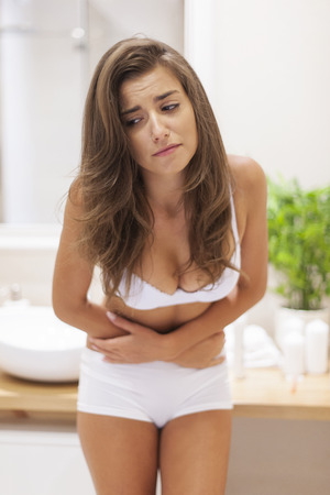 Young woman has problems with stomachache photo