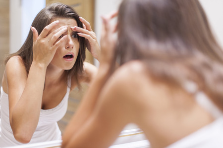 Shocked woman squeezing pimple in bathroom  Stock Photo