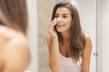 cleaning bathroom: Beautiful brunette woman removing makeup from her face