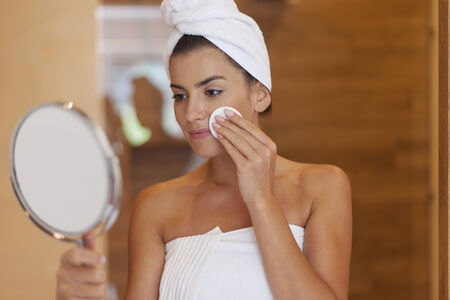 removing make up: Woman cleaning face in bathroom