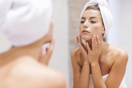 Mujer que mira en la reflexión en el espejo después de la ducha Foto de archivo