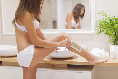 bending over: Focus woman waxing leg in bathroom  Stock Photo