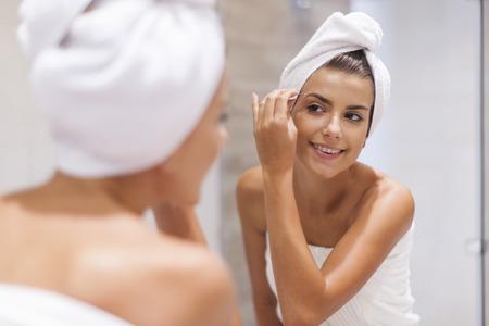 tweezing: Happy young woman tweezing eyebrows Stock Photo