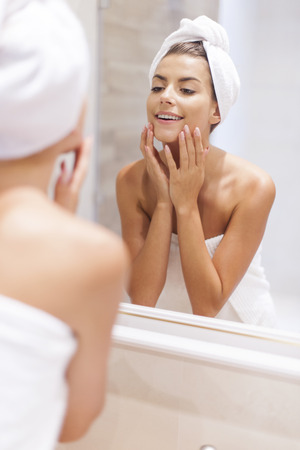 woman in shower: Woman looking on reflection in the mirror after shower
