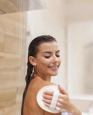 Happy young woman taking shower