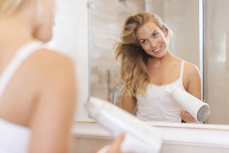 Smiling blonde woman drying hair in morning  photo