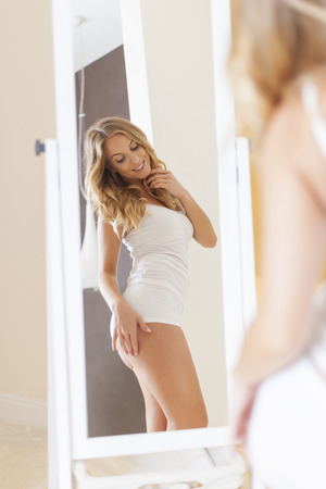 woman underwear: Blonde woman standing in front of mirror and checking her body