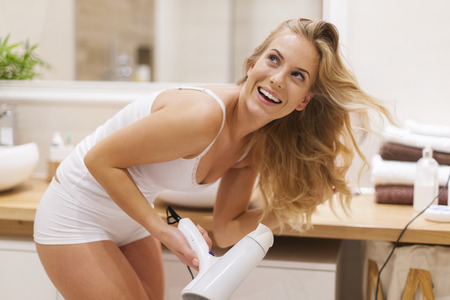 bending over: Blonde woman has fun during drying hair in bathroom
