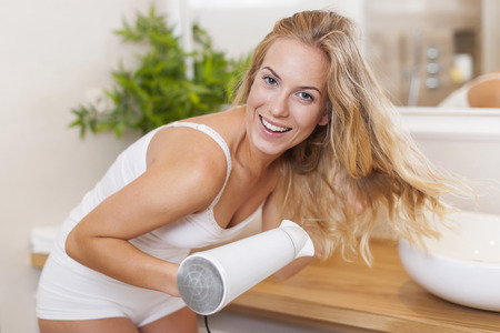 bending over: Portrait of beautiful blonde woman drying hair in bathroom