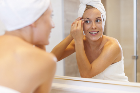 tweezing: Woman tweezing eyebrows in front of mirror  Stock Photo