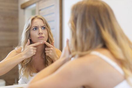 confused woman: Angry woman squeezing  pimple from face