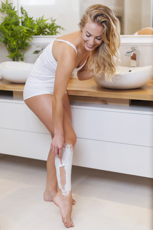 bending over: Smiling blonde woman shaving legs in bathroom
