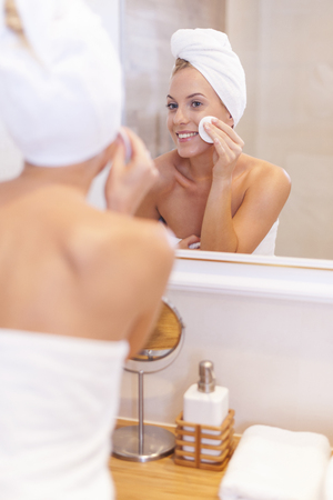 woman washing face: Woman cleaning face in front of mirror