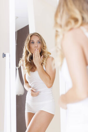 woman in the mirror: Shocked woman in front of mirror  Stock Photo