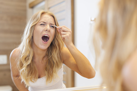 woman open mouth: Huge pain during tweezing eyebrows  Stock Photo