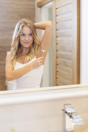 Woman shaving armpit in bathroom   photo