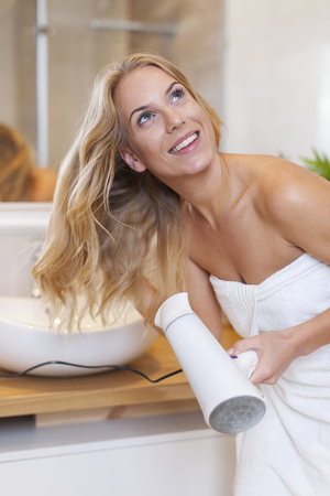 Blonde woman drying hair after the shower   photo