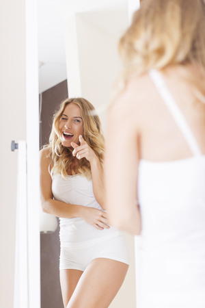 winking: Funny woman pointing on reflection in mirror