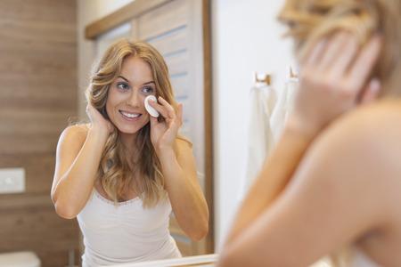 mujer maquillandose: Mujer rubia limpieza de la cara frente al espejo