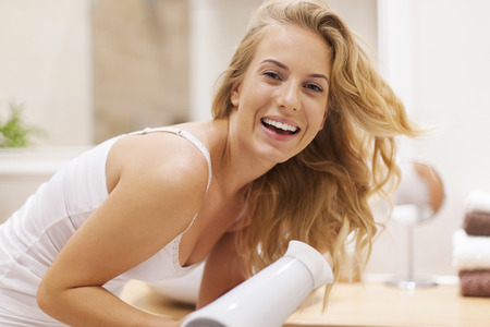 bending over: Lovely happy woman drying hair in bathroom Stock Photo